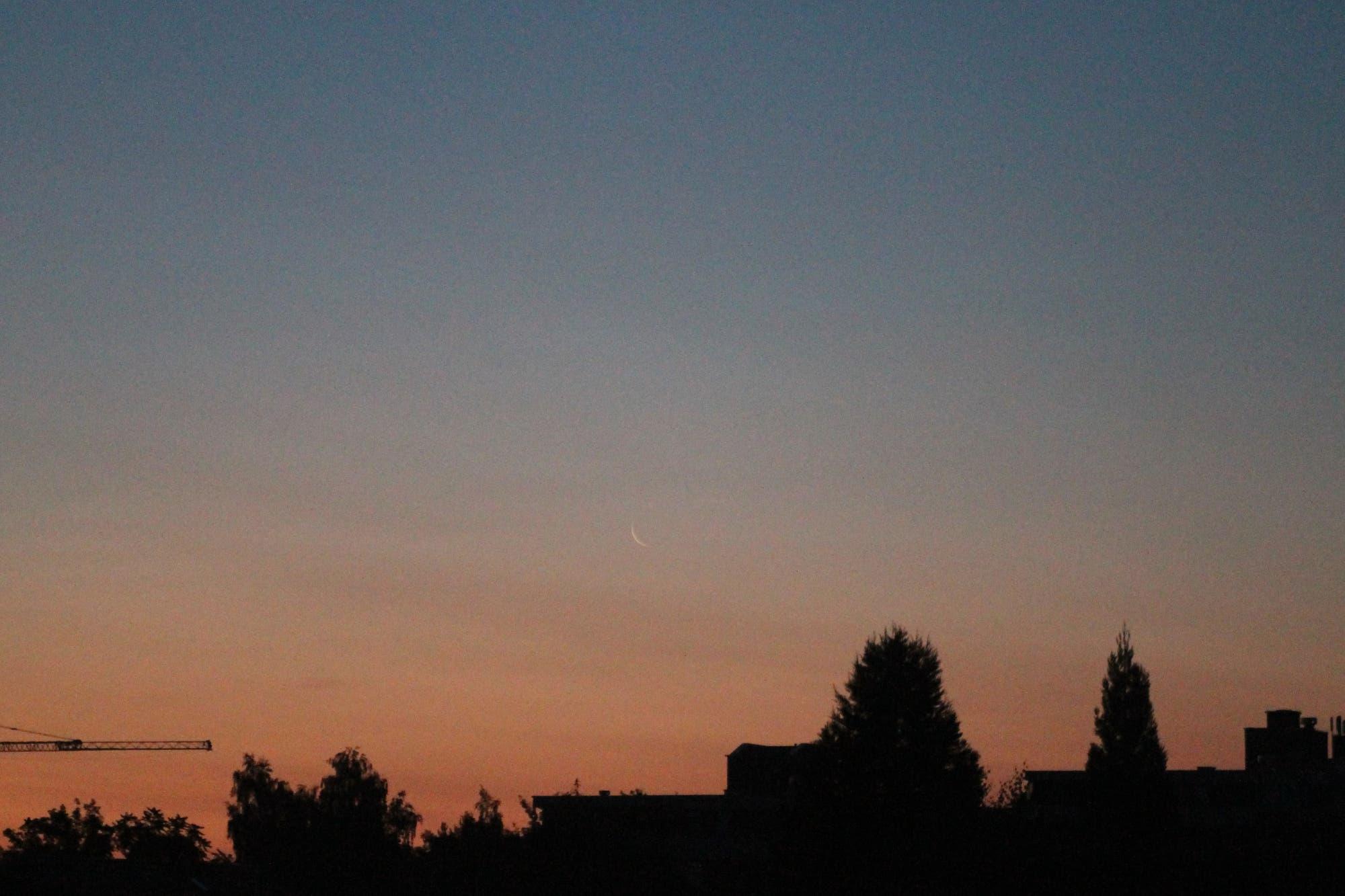 Dünne Mondsichel in der Morgendämmerung