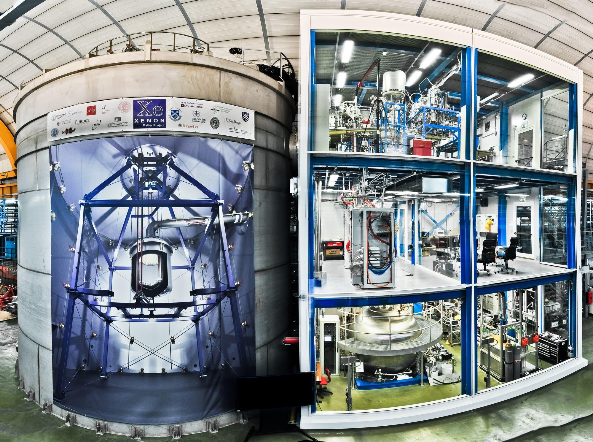 Wassertank und Gerätehaus von XENON1T – auf dem Tank ist eine Innenansicht des Tanks mit dem in der Mitte aufgehängten Detektor aufgedruckt.