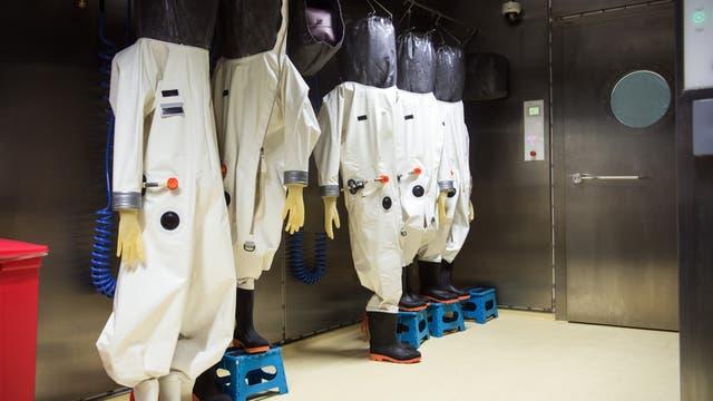 Schutzanzüge hängen im Anzugraum des S4-Labors im Robert Koch-Institut (RKI). In dem Labor der höchsten Schutzstufe vier können Mitarbeiterinnen und Mitarbeiter hochansteckende, lebensbedrohliche Krankheitserreger wie Ebola-, Lassa- oder Nipah-Viren sicher untersuchen. (Archiv)