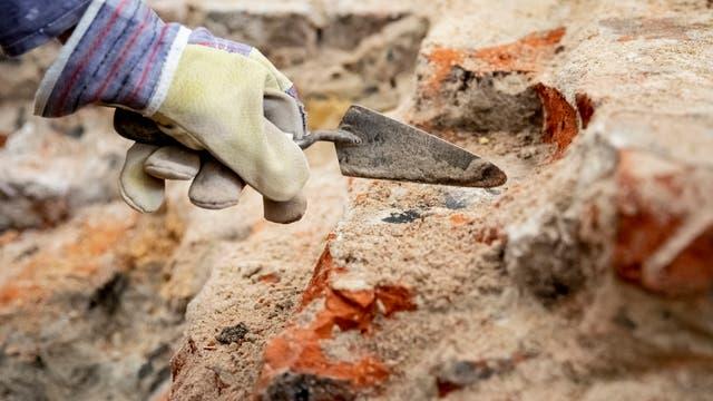 Babis Papasavvas, Restaurator und Grabungshelfer, befreit im archäologischen Grabungsfeld im Mühlendamm am Ort des historischen Molkenmarktes mit einer Kelle Steine von Sand und Schutt