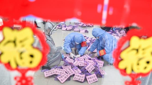Coronavirus-Epidemie in China:Drei Personen in Schutzanzügen sortieren Versorgungsgüter für Menschen in Quarantäne.