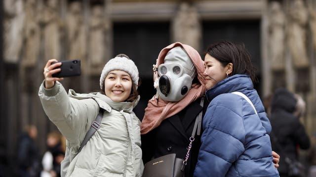 Touristen vor dem Kölner Dom posieren scherzhaft für ein Selfie mit einer Gasmaske am 29.02.2020.
