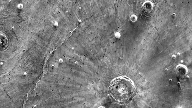 Infrarotaufnahme von der Oberfläche des Mars mit hellen Streifen, die paarweise vom Einschlagort wegzeigen