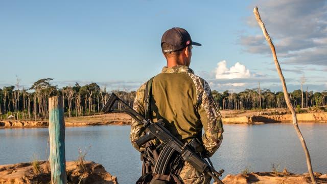 Ein Soldat bewacht La Pampa, ein Gebiet in Peru, das einst reicher Regenwald war.