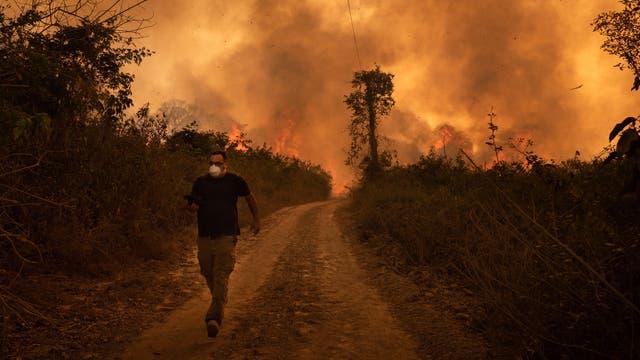 Ein Mann flieht vor den Feuern im Pantanal