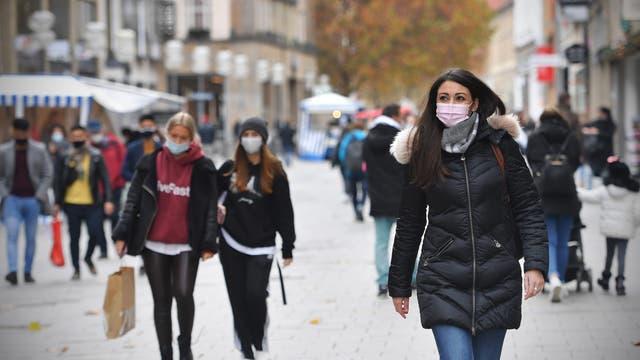 Menschen in einer Münchner Fußgängerzone tragen wegen des Coronavirus eine Maske