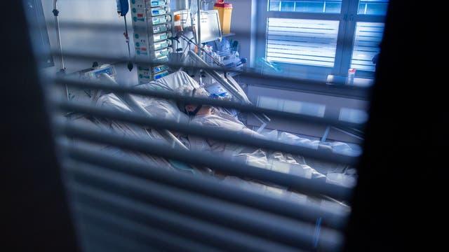 Eine an Covid-19 erkrankte Patientin liegt in einem Zimmer des besonders geschützten Teils einer Intensivstation.