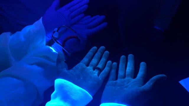 Hände mit Spritzern einer Fluoreszenzfarbe unter UV-Licht.