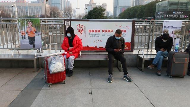 Menschen mit Masken sind am 5. Februar 2021 in der Nähe des Bahnhofs Hankou in Wuhan City, Provinz Hubei, China.