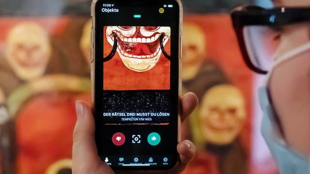 Im Badischen Landesmuseum wird vor einer Tempeltür aus Tibet aus dem 19. Jahrhundert auf einem Smartphone eine App gezeigt, mit der Museumsbesucher Kontakt zu Ausstellungsobjekten aufbauen können.