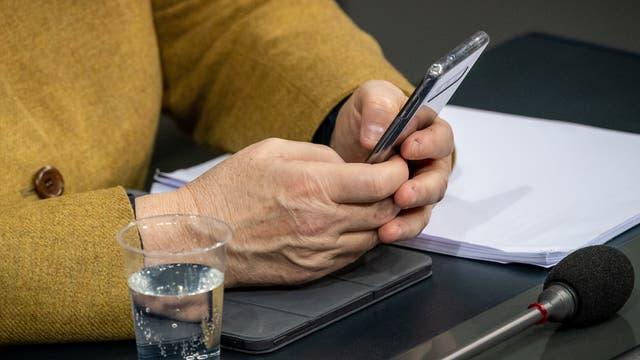 Bundeskanzlerin Angela tippt auf ihrem Smartphone im Bundestag