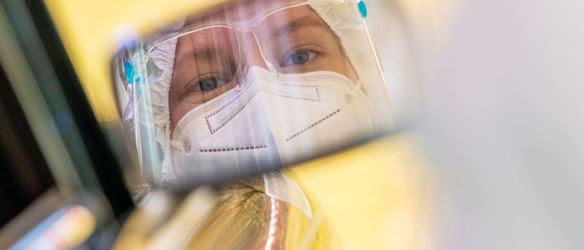Gurgel-Verfahren to Go: Eine Mitarbeiterin spiegelt sich im Außenspiegel eines Autos, das durch die Teststraße eines Corona-Testzentrums fährt.