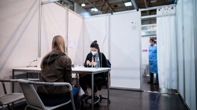 Eine Frau sitzt in der Anmeldung einer Impfkabine im Impfzentrum in Essen.