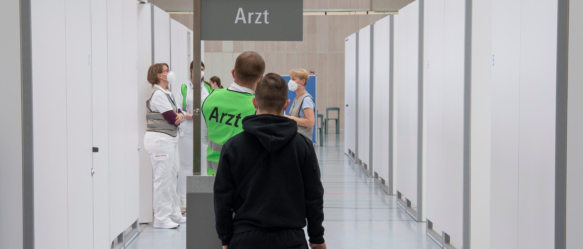 Ein Mitarbeiter der Fraport AG wird in der Impfstraße des Impfzentrum des Flughafenbetreibers Fraport von einem Arzt auf seine bevorstehende Corona-Impfung vorbereitet.