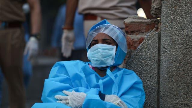 Eine Frau im Schutzanzug trauert um ihren Mann, der an den Folgen einer Infektion mit dem Coronavirus gestorben ist.