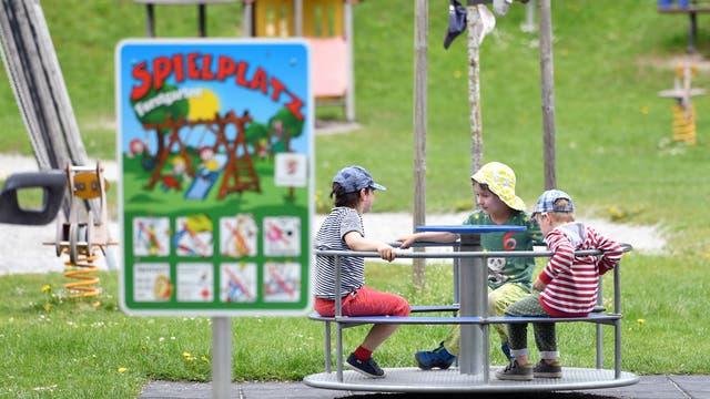 Kinder sitzen auf einem Spielplatz in einem Karussel.