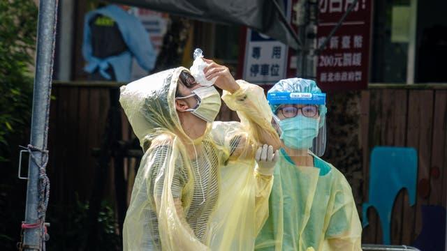 Nachdem sie in einem Testzentrum in New Taipei City auf Covid-19 getestet wurde, hält eine Person einen Eisbeutel gegen ihre Nase.