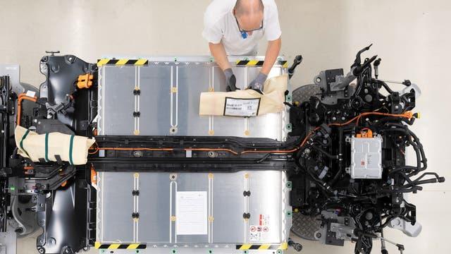 Ein Mitarbeiter von Volkswagen verkabelt den Akku an einem E-Auto.