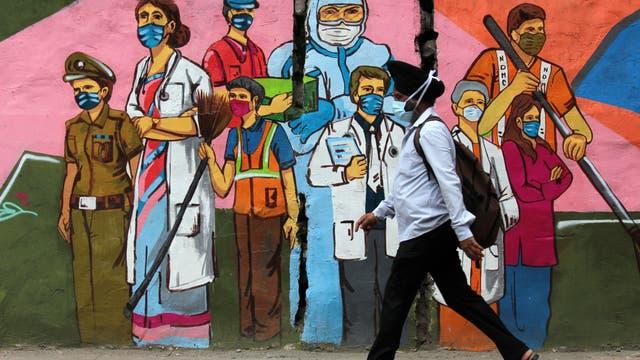 Ein Mann geht in Neu-Delhi, Indien, an einem Graffiti vorbei, das die Mitarbeiter des Gesundheitswesens würdigt.