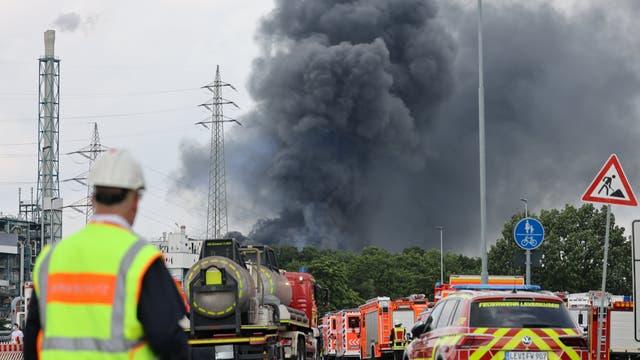 Einsatzfahrzeuge der Feuerwehr stehen am 27. Juli 2021 unweit einer Zufahrt zum Chempark, über dem eine dunkle Rauchwolke aufsteigt.
