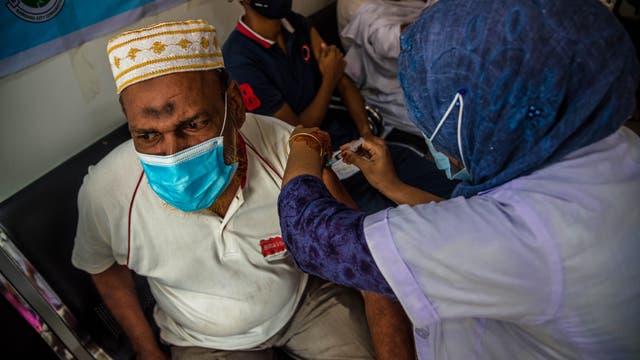 Barishal, Bangladesch: Eine Mitarbeiterin des Gesundheitssystems impft einen Mann während einer Massenimpfung mit Moderna.