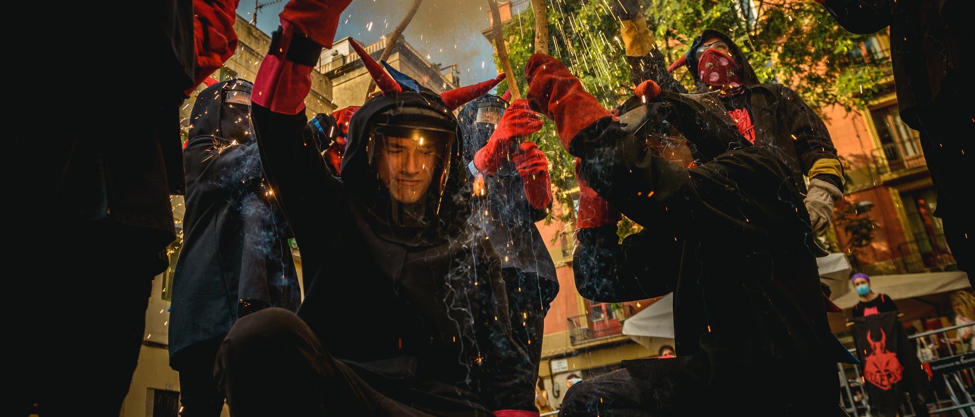Feuerläufer der katalonischen 'Diables Vell de la Gracia' in Teufelskostümen tanzen zu traditionellen Trommeln und entzünden Feuerwerk.