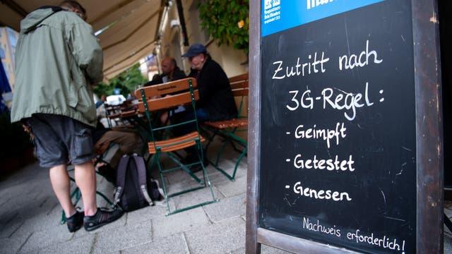 Ein Aufstellschild mit Hinweis auf die 3G-Regeln, im Hintergrund der Außenbereich eines Cafés.