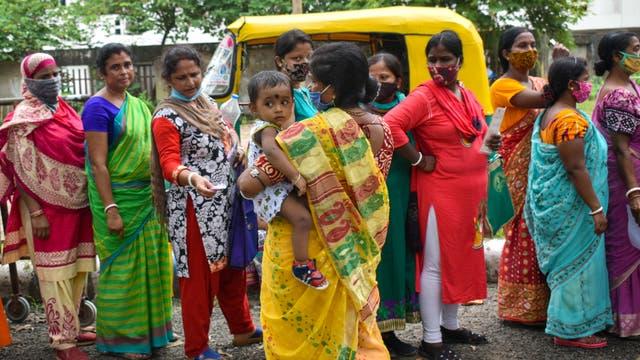 Frauen warten in einer Schlange vor einem indischen Impfcamp in Kolkata auf ihre Corona-Schutzimpfung.