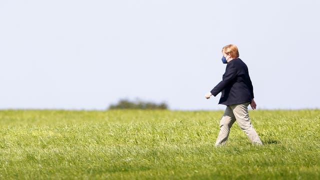 Bundeskanzlerin Angela Merkel läuft über eine grüne Wiese