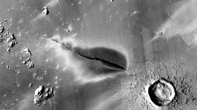 Eine dunkle Ablagerung rund um eine Spalte im Marsboden.