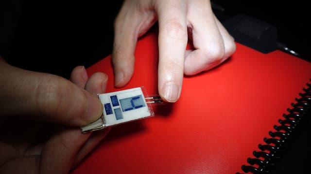 Eine Hand hält einen improvisiert anmutenden Biosensor mit LCD-Nummernanzeige gegen eine Fingerspitze.