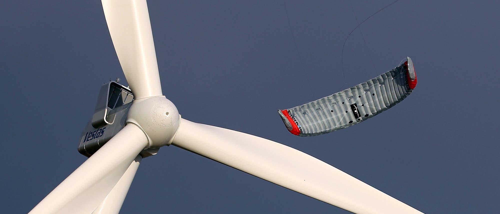 Der Prototyp eines Windenergie-Drachens hinter dem Rotor eines stationären Windrads.