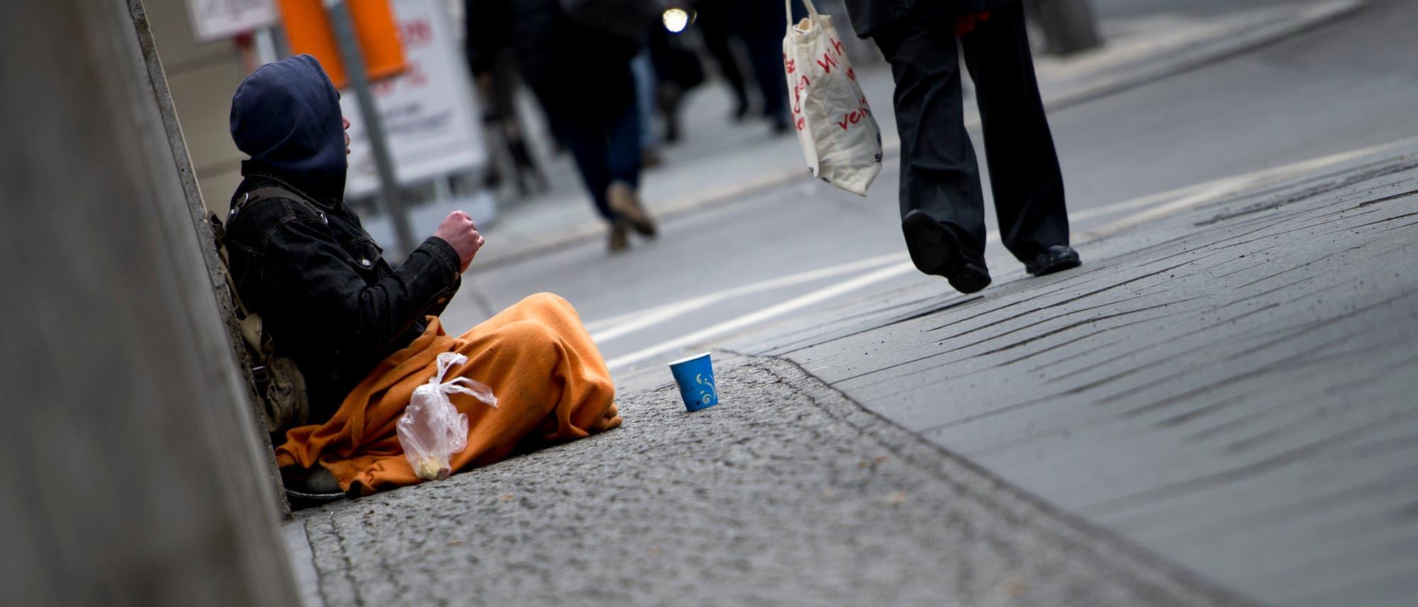 Ein Mann in Berlin bittet um eine Spende.