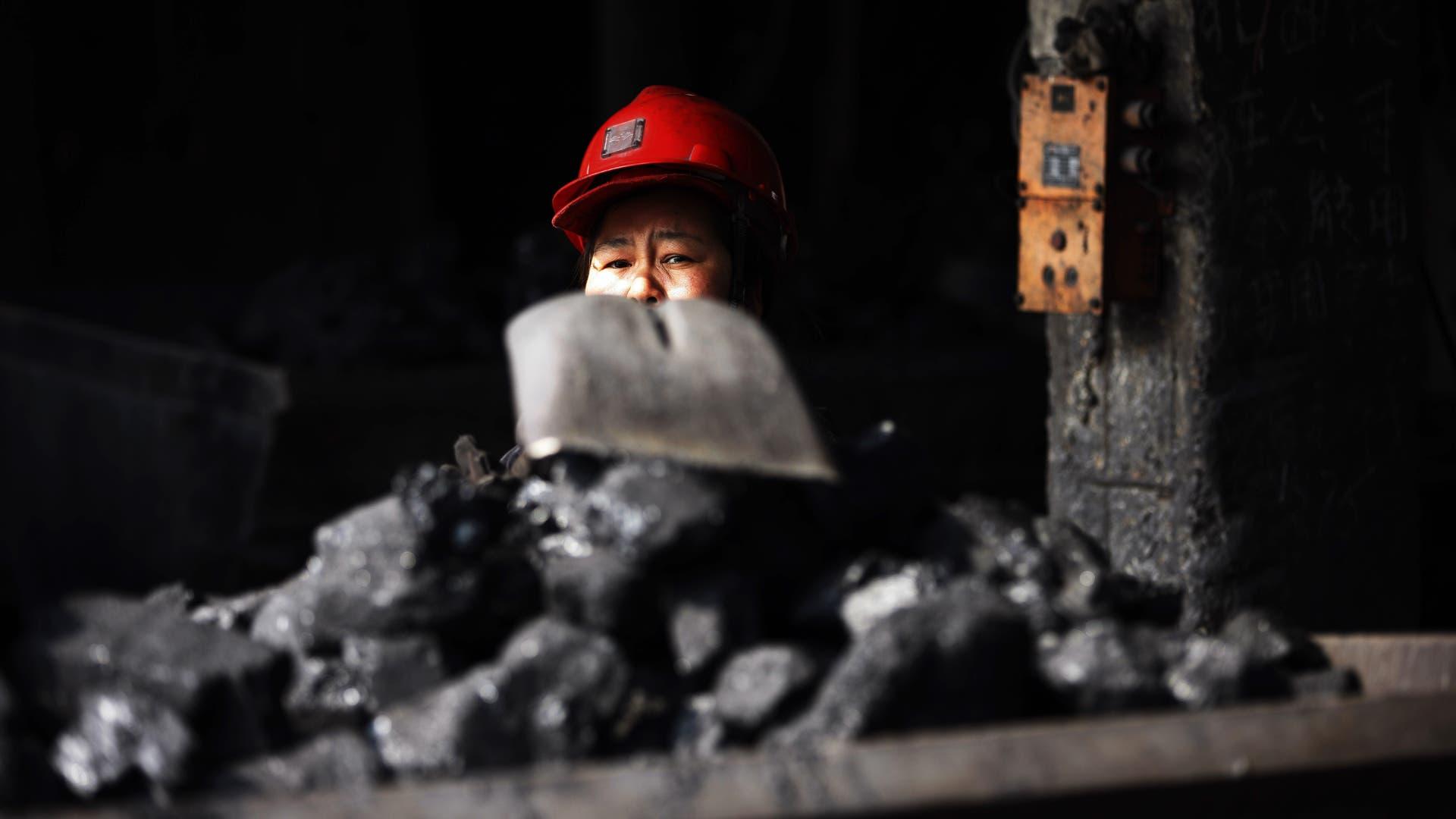 Ein chinesischer Arbeiter belädt einen Grubenwagen mit Kohle in einem Kohlebergwerk in der Stadt Huaibei in der ostchinesischen Provinz Anhui (Archiv).