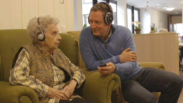 Eckart von Hirschhausen hört gemeinsam mit einer älteren Dame Musik
