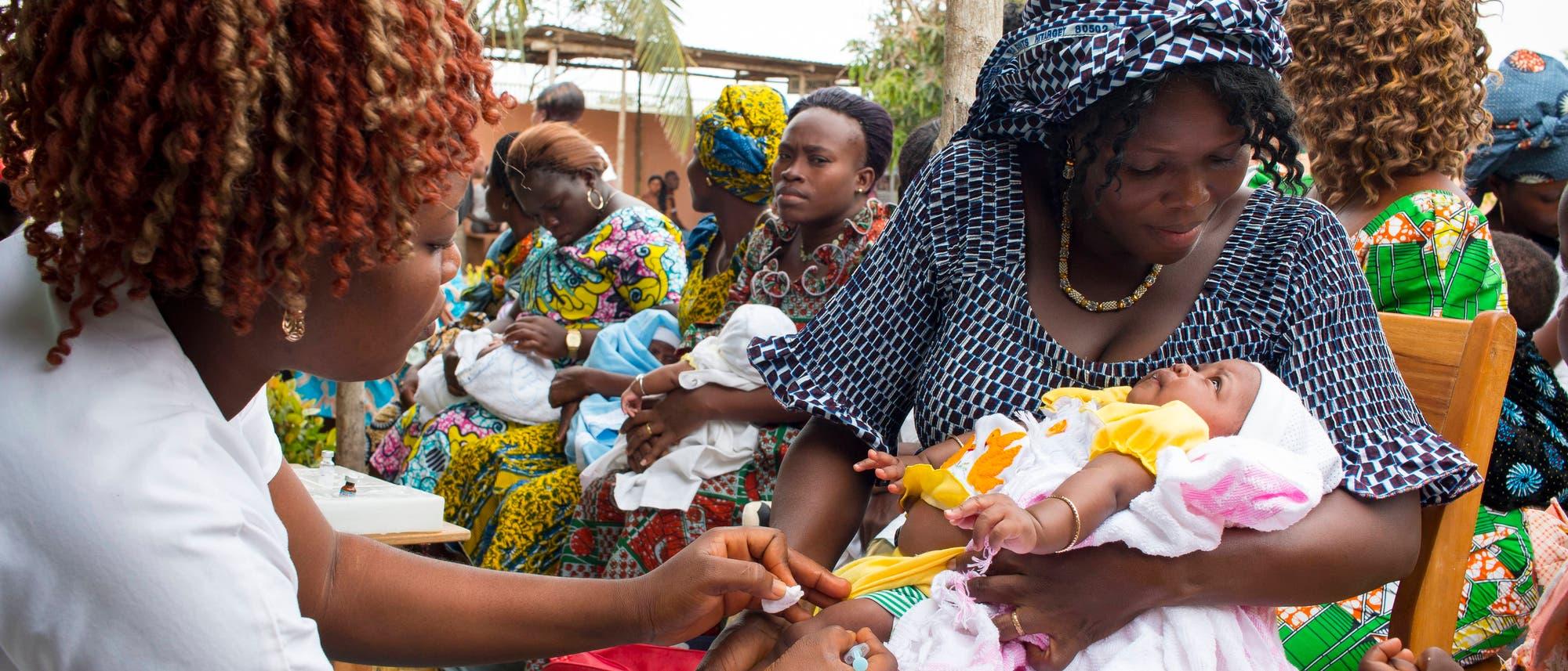 Ein Baby auf dem Arm der Mutter wird von einer Gesundheitsarbeiterin geimpft