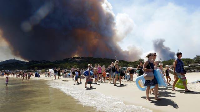 Ein Strand wird evakuiert, während hinter den Dünen im Hintergrund bereits dunkler Rauch eines Waldbrands aufsteigt.