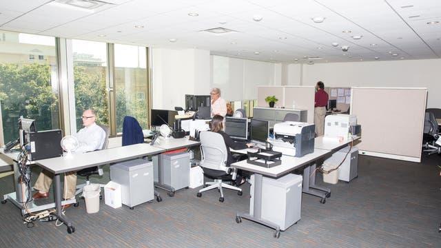 Ein Büroraum mit mehreren Tischen, auf denen sich diverse Büromaterialien und ein Computermonitor befinden.