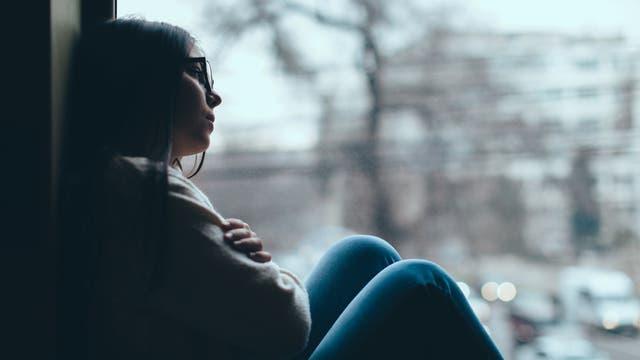 Traurige Frau sitzt am Fenster