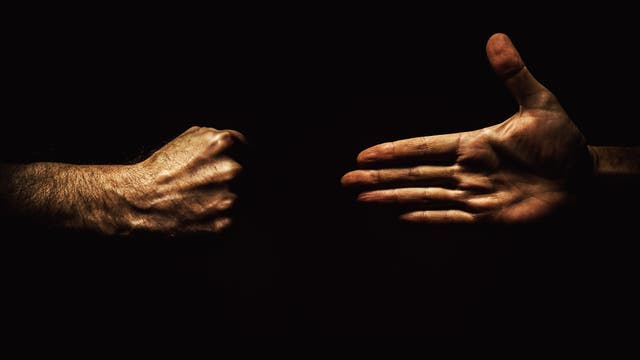 Eine offene Hand und eine geballte Faust vor schwarzem Hintergrund.