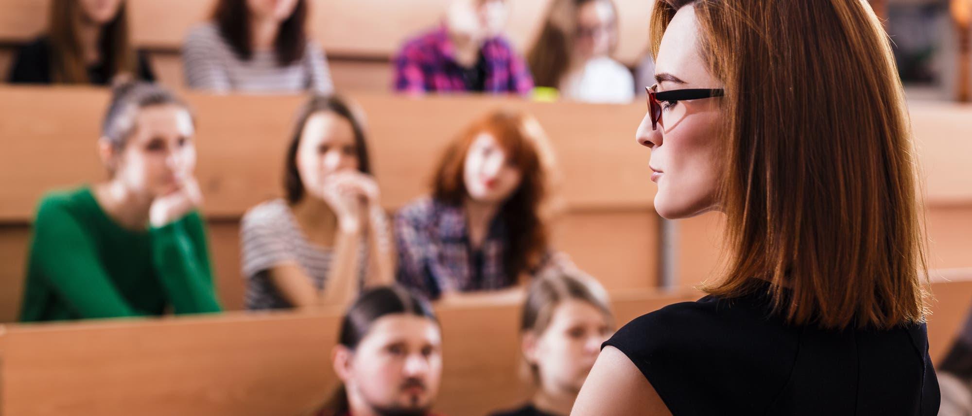 Eine Frau etwa Ende 30 im Vordergrund, Hörsaalsitze mit jungen Menschen im Hintergrund.