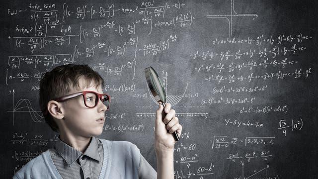 Junge mit Lupe vor vollgeschriebener Tafel mit Matheformeln