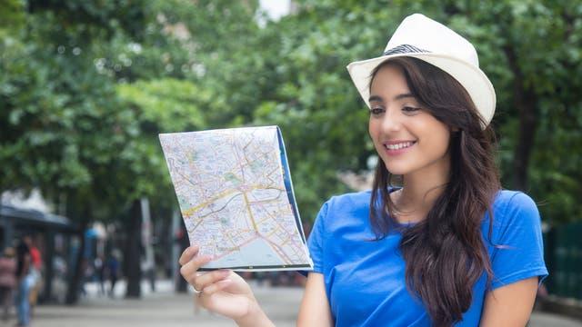 Eine junge Frau in blauem Top betrachtet einen traditionellen Stadtplan auf Papier, möglicherweise aus historischem Interesse.