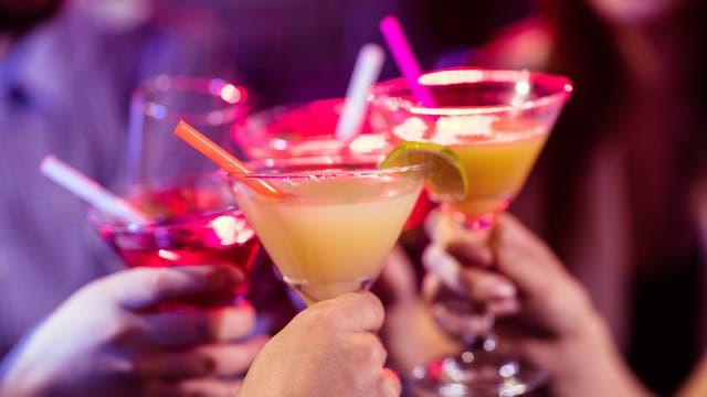 Freunde stoßen in einer Bar mit Cocktails an