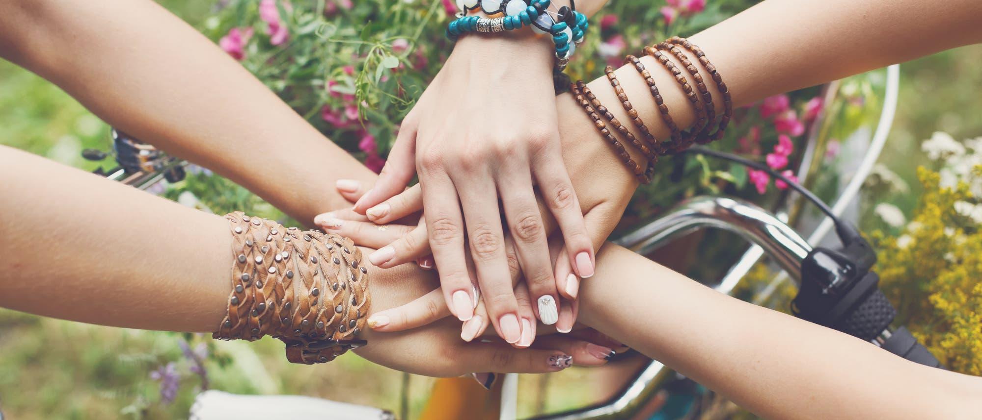 Mehrere Mädchen legen die Hände aufeinander