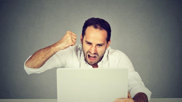 Typ sitzt brüllend vorm Laptop und schwenkt die Faust. Oder wie wir es nennen: Windows-Update.