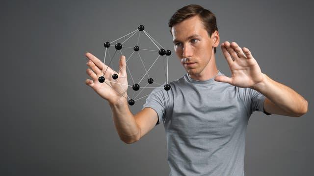 Ein Mann im grauen T-Shirt steht neben einem molekülähnlichen Dodekaeder aus Kugeln und Stäben.