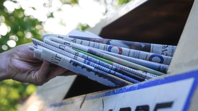Eine Hand schiebt einen Stapel Zeitungen durch den Schlitz eines Altpapiercontainers.