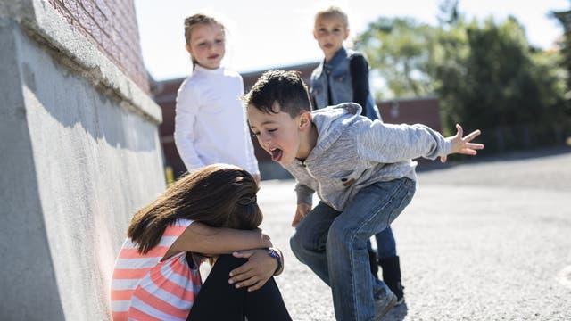 Eine Gruppe Schüler mobbt ein Mädchen