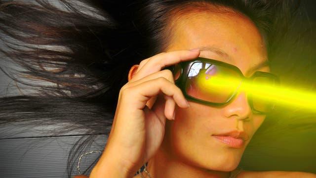 Eine junge Frau mit futuristischer Brille und ins Bild montiertem Laserstrahl.